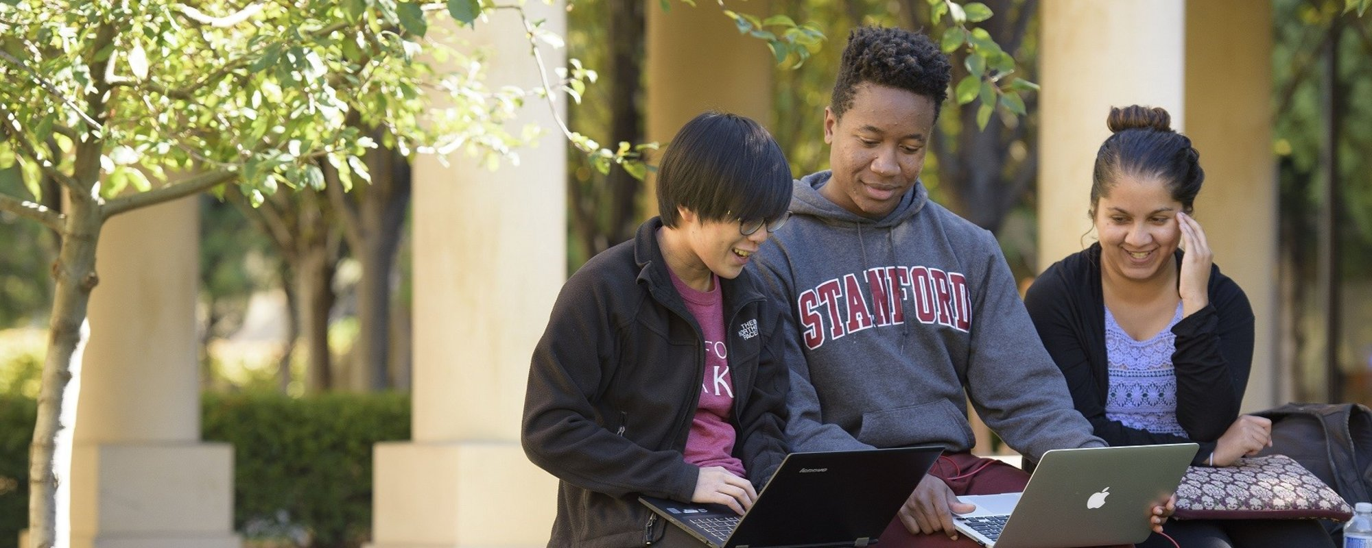 Three students working outside together with laptops. One student is wearing a Stanford sweater.