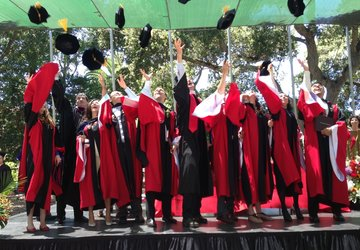 students throwing mortarboards in the air post-graduation