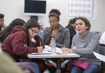 Students working at a table in class; one student looks confused.