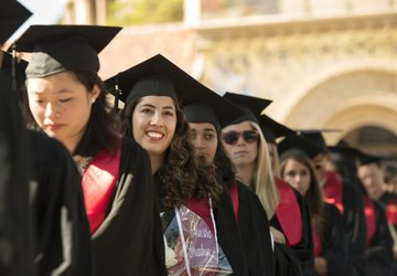 Students in cap and gown lined up under Stanford arches, smiling student in focus